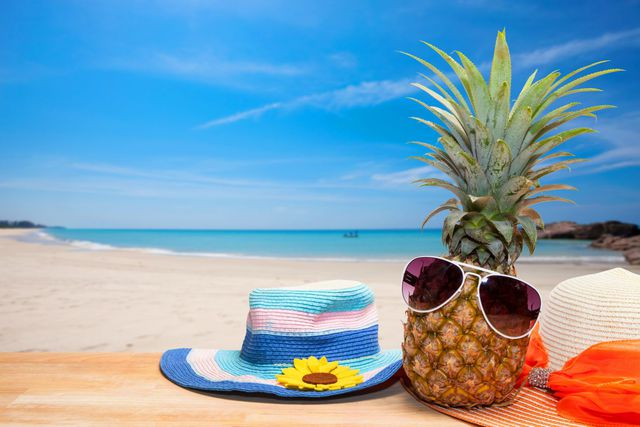 pineapple with sunglasses and hat beach on wood,concept summer background.